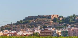 Vecchio contro nuovo Fortifichi nel fondo, città in priorità alta dalla strada principale in Spagna rurale Fotografia Stock