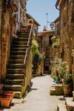 Vecchio cortile in Pitigliano con i vasi con i fiori e con la st Fotografie Stock Libere da Diritti
