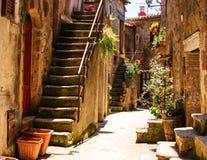 Vecchio cortile in Pitigliano con i vasi con i fiori e con la st Immagini Stock Libere da Diritti