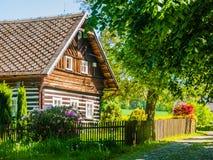 Vecchio cottage armato in legno tradizionale con il giardino floreale verde fertile romantico e idilliaco con il recinto di legno fotografia stock
