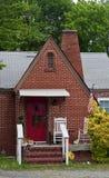 Vecchio cottage del mattone con il portello rosso Immagini Stock