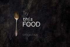 Vecchio cucchiaio della fattoria con la prova del testo questo alimento sulla vista superiore concreta Immagine Stock