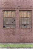 Vecchio dare segni della costruzione di mattone rosso dell'abbandono con due ha rotto le finestre fotografia stock