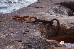 Vecchio destructed la catena arrugginita riparata in un pezzo di calcestruzzo immagini stock libere da diritti