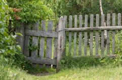 Vecchio di legno un wicket nel recinto su un fondo degli alberi verdi Immagine Stock Libera da Diritti