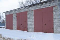 Vecchio di pietra del garage con i portoni rossi del ferro Fotografia Stock