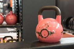 Vecchio e grande kettlebell rosa usato su un banco in una palestra Palestra ed attrezzatura di forma fisica fotografia stock
