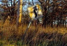 Vecchio e segno incrinato della curva avanti che inclina lateralmente lungo una strada campestre nella sera con il sole dorato ch Immagine Stock