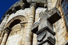 Vecchio ed incrocio di pietra cristiano stagionato con l'iscrizione 1643 con la chiesa nel fondo Immagine Stock