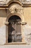 Vecchio entrata anteriore invecchiata della porta arco di legno di costruzione medievale decorata con la pietra sul fondo dello s Fotografia Stock
