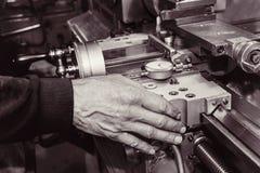 Vecchio equipaggia la mano su una vecchia macchina del tornio fotografie stock