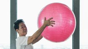 Vecchio esercizio sano senior asiatico della donna con la palla relativa alla ginnastica rosa Immagini Stock