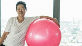 Vecchio esercizio sano senior asiatico della donna con la palla relativa alla ginnastica rosa Fotografia Stock Libera da Diritti