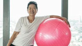 Vecchio esercizio sano senior asiatico della donna con la palla relativa alla ginnastica rosa Fotografia Stock