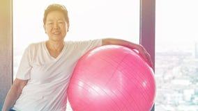 Vecchio esercizio sano senior asiatico della donna con la palla relativa alla ginnastica rosa Fotografie Stock Libere da Diritti