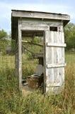 Vecchio fabbricato annesso traballante con la copertura di sedile della toilette Fotografia Stock