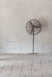 Vecchio fan nero contro una parete di grey della sbucciatura Immagini Stock