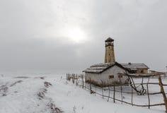 Vecchio faro di legno al bordo del porto congelato con il cielo nuvoloso Immagine Stock