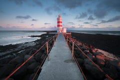 Vecchio faro in Gardur, Keflavik, Islanda Cielo nuvoloso e mare mosso Bello tramonto Cerchio dorato, la maggior parte del posto p fotografie stock libere da diritti