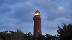 Vecchio faro Shinning sopra l'abetaia prima del tramonto Torre illuminata con forte luce d'avvertimento Faro costruito da Br ross stock footage