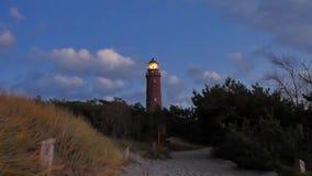 Vecchio faro Shinning sopra l'abetaia prima del tramonto Torre illuminata con forte luce d'avvertimento Faro costruito da Br ross video d archivio