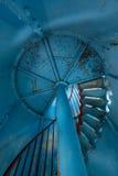 Vecchio faro sull'interno Scale rosse di spirale del ferro, finestra rotonda e parete blu Immagini Stock
