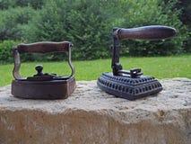 Vecchio ferro antico arrugginito due con la maniglia di legno sulla parete dell'arenaria fotografia stock