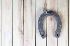 Vecchio ferro di cavallo arrugginito che appende su un fondo di legno Fotografia Stock