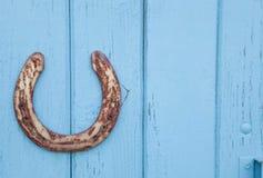 Vecchio ferro di cavallo arrugginito su fondo blu di legno Fotografie Stock