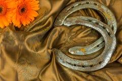 Vecchio ferro di cavallo con i fiori rossi della gerbera Fotografia Stock Libera da Diritti