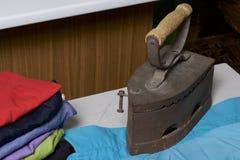 Vecchio ferro, riscaldato dai carboni caldi Individuato su tessuto di tela Stando su una tavola da stiro Accanto ad una pila di c immagini stock