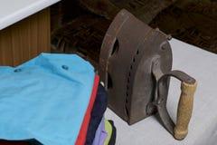 Vecchio ferro, riscaldato dai carboni caldi Individuato su tessuto di tela Stando su una tavola da stiro Accanto ad una pila di c fotografie stock