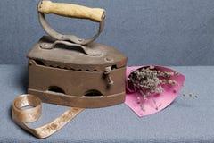 Vecchio ferro, riscaldato dai carboni caldi Individuato su tessuto grigio Vicino ad un mazzo dei fiori e del nastro secchi per la fotografie stock