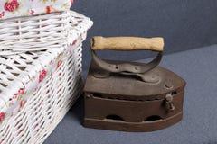 Vecchio ferro, riscaldato dai carboni caldi Individuato su tessuto grigio Vicino sono i canestri di vimini fotografia stock