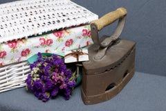 Vecchio ferro, riscaldato dai carboni caldi Individuato su tessuto grigio Vicino sono i canestri di vimini, un mazzo dei fiori se immagine stock