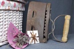 Vecchio ferro, riscaldato dai carboni caldi Individuato su tessuto grigio Vicino sono i canestri di vimini, un mazzo dei fiori se fotografie stock