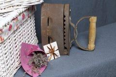 Vecchio ferro, riscaldato dai carboni caldi Individuato su tessuto grigio Vicino sono i canestri di vimini, un mazzo dei fiori se fotografia stock