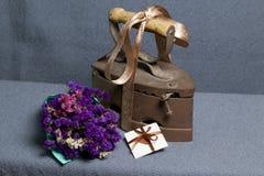 Vecchio ferro, riscaldato dai carboni caldi Individuato su tessuto grigio Vicino sono il mazzo dei fiori secchi e una cartolina d immagini stock