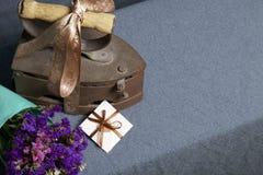 Vecchio ferro, riscaldato dai carboni caldi Individuato su tessuto grigio Vicino sono il mazzo dei fiori secchi e una cartolina d fotografie stock