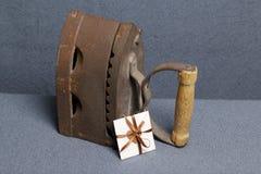 Vecchio ferro, riscaldato dai carboni caldi Individuato su tessuto grigio Vicino una cartolina d'auguri fotografie stock