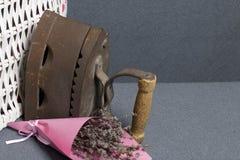 Vecchio ferro, riscaldato dai carboni caldi Individuato vicino all'i canestri di vimini Vicino ad un mazzo dei fiori secchi fotografia stock
