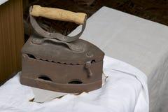 Vecchio ferro, riscaldato dai carboni caldi Stando su una camicia bianca bruciata Panno bruciato visibile immagine stock