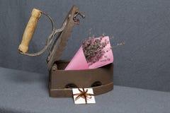 Vecchio ferro, riscaldato dai carboni caldi Un mazzo dei fiori secchi è incastonato nel ferro leggermente aperto Vicino è una car fotografia stock libera da diritti