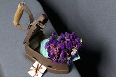 Vecchio ferro, riscaldato dai carboni caldi Un mazzo dei fiori secchi è incastonato nel ferro leggermente aperto Vicino è una car fotografie stock