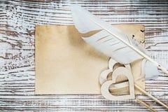 Vecchio foglio di carta i cuori di legno della piuma sul bordo di legno d'annata h Fotografie Stock Libere da Diritti