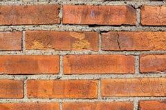 Vecchio fondo del muro di mattoni macchiato Weathered con cemento e piccole pietre fra la regolazione del mattone immagine stock