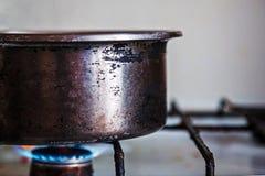 Vecchio fornello graffiato del metallo disposto su una stufa di gas Fotografia Stock