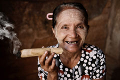 Vecchio fumo asiatico corrugato felice della donna Immagini Stock