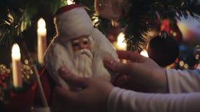 Vecchio giocattolo d'annata Santa Claus, albero di Natale vicino stante, mani di natale della donna video d archivio