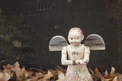 Vecchio giocattolo di angelo sulla tomba di un bambino fotografia stock